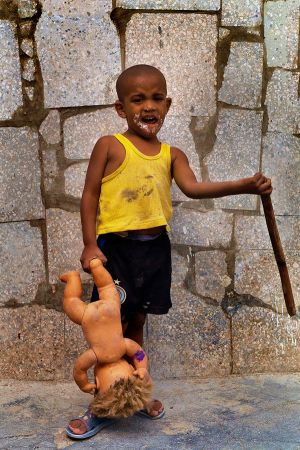 BOY PLAYING WITH A DOLL AND STICK IN A BARRIO IN HAVANA, CUBA