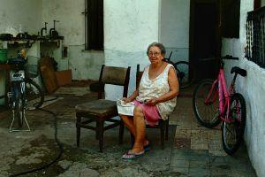 LADY IN YARD OF FAMILY BUSINESS OF BIKE REPAIR