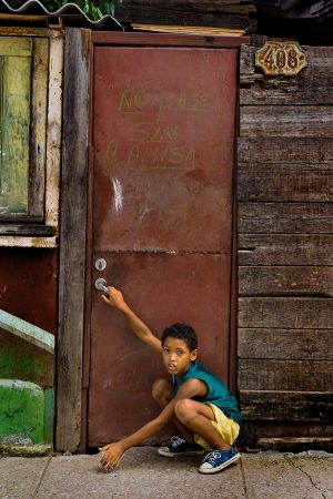 BOY PLAYING BY A DOOR OF A PALADAR IN A POOR NEIGHBORHOOD