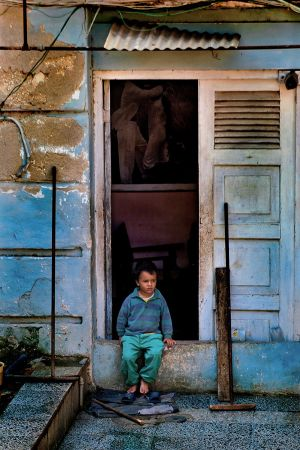 BOY SITTING IN DOORWAY TO HIS HOME